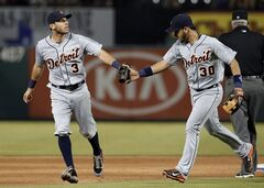 Detroit Tigers' Ian Kinsler (3) and Eugenio Suarez (30) celebrate after Texas Rangers' Michael Choice hit into a double play in the fifth inning of a baseball game, Thursday, June 26, 2014, in Arlington, Texas. The Tigers won 6-0. (AP Photo/Tony Gutierrez)