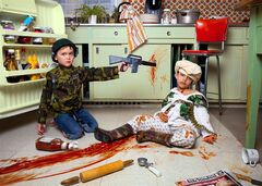 One of Jonathan Hobin's newest provocative photographs, GOT HIM!, a marine with a toy gun shoots Osama Bin Laden in a messy ketchup-blood scene beside a kitchen fridge. Hobin's exhibit