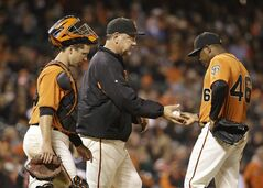 San Francisco Giants relief pitcher Santiago Casilla, right, hands the ball to manager Bruce Bochy, center, and heads for the dugout as catcher Buster Posey, left, looks on in the ninth inning of a baseball game against the Miami Marlins Friday, May 16, 2014, in San Francisco. Miami won the game 7-5 and Casilla was the losing pitcher. (AP Photo/Eric Risberg)