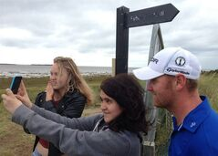 In this photo taken with a mobile phone, spectators take a selfie with John Singleton of England after his television interview at the Royal Liverpool golf club, Hoylake, England, Wednesday July 16, 2014 where the British Open Golf championship will start Thursday July 17. (AP Photo/Paul Newberry)