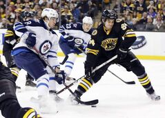 Winnipeg Jets' Alex Burmistrov  tries to get a shot on goal as Boston Bruins' Adam McQuaid defends during the first period.