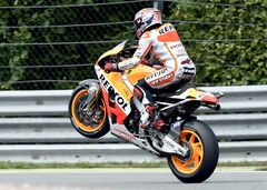 First placed Marc Marquez from Spain lifts his front wheel after the MotoGP race at the Sachsenring circuit in Hohenstein-Ernstthal, Germany, Sunday, July 13, 2014. (AP Photo/Jens Meyer)