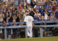 Fans cheer as Los Angeles Dodgers starting pitcher Hyun-Jin Ryu leaves the field after being relieved in the eighth inning of a baseball game against the Cincinnati Reds, Monday, May 26, 2014, in Los Angeles. The Dodgers won 4-3. (AP Photo/Gus Ruelas)