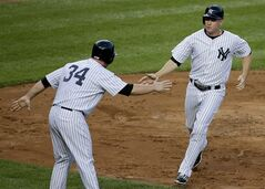 New York Yankees' Chase Headley, right, is greeted by Brian McCann after scoring on an errant throw by Cleveland Indians second baseman Jason Kipnis (22) in the first inning of a baseball game, Friday, Aug. 8, 2014, in New York. (AP Photo/Julie Jacobson)