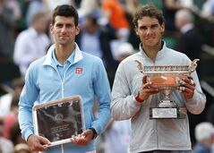 Spain's Rafael Nadal, right, holds the trophy after winning the final of the French Open tennis tournament against Serbia's Novak Djokovic, left, at the Roland Garros stadium, in Paris, France, Sunday, June 8, 2014. Nadal won in four sets 3-6, 7-5, 6-2, 6-4. (AP Photo/Darko Vojinovic)
