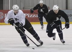 At right, Winnipeg Jets centre Bryan Little and Dallas Stars centre Ryan Garbutt (a former Winnipegger) chase after puck during practice at the MTS Iceplex Friday as the NHL lockout continues.
