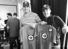 Winnipeg Jets fans Adam Cunliffe (left) and Jacques Auger show off their newly acquired Jets merchandise in the team store at the MTS Centre Friday.