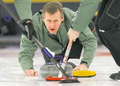 Bob Sigurdson curls in the provincial curling playdowns at Charleswood Curling Club Sunday.