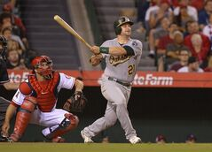 Oakland Athletics' Stephen Vogt, right, hits a two-run home run as Los Angeles Angels catcher Chris Iannetta looks on during the sixth inning of a baseball game, Wednesday, June 11, 2014, in Anaheim, Calif. (AP Photo/Mark J. Terrill)