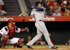 Tampa Bay Rays' James Loney, right, hits a single to score Evan Longoria with Los Angeles Angels catcher Hank Conger, left, watching in the seventh inning of a baseball game on Friday, May 16, 2014, in Anaheim, Calif. (AP Photo/Alex Gallardo)