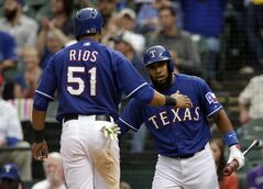 Texas Rangers' Alex Rios (51) is congratulated by Elvis Andrus, right, after Rios scored on a Leonys Martin single in the second inning of a baseball game against the Colorado Rockies, Thursday, May 8, 2014, in Arlington, Texas. (AP Photo/Tony Gutierrez)