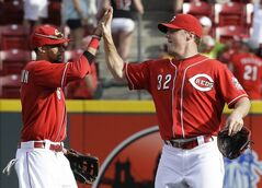 Cincinnati Reds right fielder Jay Bruce (32) high-fives center fielder Billy Hamilton after they defeated the Toronto Blue Jays 11-1 in a baseball game on Saturday, June 21, 2014, in Cincinnati. Bruce hit a home run in the game. (AP Photo/Al Behrman)