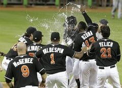 Miami Marlins' Jeff Baker, center, is sprayed with water by Marcell Ozuna (13) after driving in the winning run with a single to score Adeiny Hechavarria in the ninth inning during a baseball game against the Washington Nationals, Monday, July 28, 2014, in Miami. The Marlins defeated the Nationals 7-6. (AP Photo/Lynne Sladky)