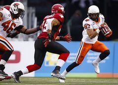 B.C. Lions' Marco Iannuzzi, runs with the ball as Calgary Stampeders' Karl McCartney, closes in during first quarter CFL football action in Calgary, Alta., Friday, Aug. 1, 2014. THE CANADIAN PRESS/Jeff McIntosh