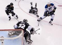 St. Louis Blues right wing Chris Stewart, right, scores on Los Angeles Kings goalie Jonathan Quick, lower left, as Los Angeles Kings defenseman Slava Voynov of Russia dives for it and defenseman Willie Mitchell looks on during the third period in Game 3 of an NHL hockey Stanley Cup second-round playoff series, Thursday, May 3, 2012, in Los Angeles. The Kings won 4-2. (AP Photo/Mark J. Terrill)