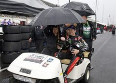 Kurt Busch drives a cart back to the garage area under an umbrella as rain halted practice for the Indianapolis 500 IndyCar auto race at the Indianapolis Motor Speedway in Indianapolis, Tuesday, May 13, 2014. (AP Photo)