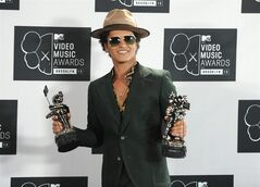 FILE - In this Aug. 25, 2013 file photo, Bruno Mars poses backstage with the award for Best Male Video for