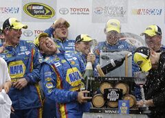 FILE - In this June 23, 2013, file photo, Martin Truex Jr., second from left, sprays his team with champagne as they celebrate in Victory Lane after winning the NASCAR Sprint Cup series auto race in Sonoma, Calif. Truex returns this weekend aiming for another win, but so much else has changed. He'll bring a new team, different car, and whole new sense of desperation to win and try and force his way into the Chase for the Sprint Cup championship.(AP Photo/Eric Risberg, File)