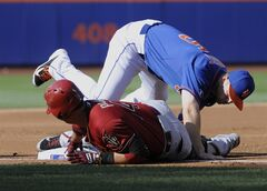 Arizona Diamondbacks' Martin Prado slides into third base with a RBI-triple as New York Mets third baseman David Wright takes the throw during the second inning of the second game of a baseball double-header Sunday, May 25, 2014, at Citi Field in New York. (AP Photo/Bill Kostroun)