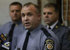 Pennsylvania state trooper Jeff Pettuci talks during a news conference at the Geeseytown Fire Company about shootings along a nearby rural road that left four people dead and three Pennsylvania State troopers injured on Friday, Dec. 21, 2012, in Geeseytown, Pa. Pennsylvania State police Lieutenant George Bivens, is at right, and Capt. Maynard Gray is at left. A man fatally shot a woman decorating for a children's Christmas party at a tiny church hall and killed two men elsewhere in the rural central Pennsylvania township before he was fatally shot in a gunfight with state troopers. (AP Photo/Keith Srakocic)