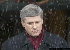Prime Minister Stephen Harper speaks to reporters as snow falls in Ottawa Thursday.