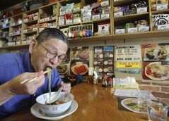 "In this Tuesday, Aug. 19, 2014 photo, Japanese instant ramen noodle expert Masaya ""Sokusekisai"" Oyama, 55, slurps noodles at a shop and restaurant specialized only in varieties of instant noodles in Tokyo. Oyama knows a lot about the instant noodle. He eats more than 400 instant noodles a year, and he usually goes by his nickname ""Sokusekisai,"" which means ""instant."" He agrees eating only instant noodles is not good for your health, because eating one thing all the time isn't healthy, no matter what it is. ""You need nutritional balance,"" he said. ""You should eat other things, too."" (AP Photo/Koji Sasahara)"