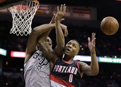 San Antonio Spurs' Boris Diaw, left, of France, and Portland Trail Blazers' Damian Lillard (0) battle for a rebound during the first half on an NBA basketball game, Friday, Jan. 17, 2014, in San Antonio. (AP Photo/Eric Gay)