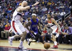 Sacramento Kings point guard Isaiah Thomas, center, is defended by Washington Wizards center Marcin Gortat, left, and forward Trevor Ariza during the first half of an NBA basketball game, Sunday, Feb. 9, 2014, in Washington. (AP Photo/ Evan Vucci)
