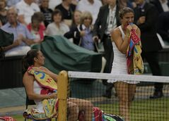 Sara Errani of Italy, right, and Roberta Vinci of Italy celebate defeating Timea Babos of Hungary and Kristina Mladenovic of France in the women's doubles final at the All England Lawn Tennis Championships at Wimbledon, London, Saturday July 5, 2014. (AP Photo/Pavel Golovkin)
