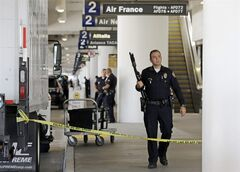 FILE - This Nov. 1, 2013 file photo shows police standing stand guard in Terminal 2 at Los Angeles International Airport. A union representative for the police force that secures Los Angeles International Airport told members of Congress Thursday he still has concerns about a manpower shortage and a lack of coordination and communication with the Transportation Security Administration nearly seven months after a gunman killed a TSA officer and injured three others. (AP Photo/Reed Saxon, File)