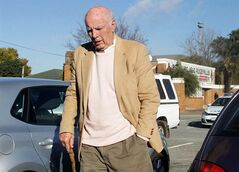 Bob Hewitt, the former Grand Slam doubles champion and one-time tennis hall of famer, is seen outside the magistrates court in Boksburg, South Africa, Friday, June 6, 2014. The lawyer representing Bob Hewitt says he has been charged with rape and sexual assault of minors and will go to trial in February. Attorney Alwyn Griebenow told The Associated Press that Hewitt denies two charges of rape and one of sexual assault of girls he coached in South Africa decades ago. Griebenow said Hewitt attended Boksburg Magistrate's Court near Johannesburg on Friday and told the court he understood the charges. He was not asked to enter a plea, but Griebenow said he would plead not guilty to all three charges at his trial. The Australian-born Hewitt, now 74, won nine grand slam doubles and six mixed doubles titles in the 1960s and 1970s.(AP Photo/Nokuthula Mbatha - The Star) SOUTH AFRICA OUT