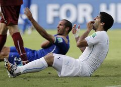 FILE - In this June 24, 2014 file photo, Uruguay's Luis Suarez holds his teeth after biting Italy's Giorgio Chiellini's shoulder during the group D World Cup soccer match between Italy and Uruguay in Natal, Brazil. Sinking teeth into the shoulder of Giorgio Chiellini in a group-stage game led to a four-month ban from all football for the Uruguay striker. (AP Photo/Ricardo Mazalan, File)