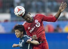 Toronto FC Doneil Henry, right, heads the ball against Whitecaps Nicolas Mezquida, left, in Toronto on May 7, 2014. THE CANADIAN PRESS/Nathan Denette