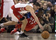 Toronto Raptors guard Greivis Vasquez (left) and Atlanta Hawks guard Dennis Schroder (17) battle for a loose ball during first half NBA action in Toronto on Wednesday February 12, 2014. THE CANADIAN PRESS/Frank Gunn