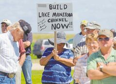 Twin Lakes Beach resident Lilli Schneider (holding placard) attends a gathering of farmers and residents demanding immediate action to build a channel out of Lake Manitoba. Schneider rebuilt her home 27 metres from where it originally stood before the 2011 flooding.