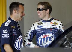 Brad Keselowski, right, talks to crew chief Paul Wolfe in the garage during practice for the Daytona 500 NASCAR Sprint Cup Series auto race Wednesday, Feb. 20, 2013, in Daytona Beach, Fla. (AP Photo/Terry Renna)