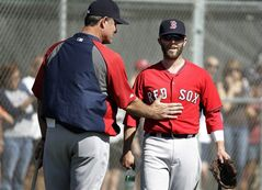 Boston Red Sox manager John Farrell, left, gives Red Sox second baseman Dustin Pedroia, right, a pat on the stomach during spring training baseball practice, Monday, Feb. 17, 2014, in Fort Myers, Fla. (AP Photo/Steven Senne)