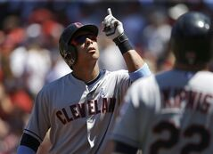 Cleveland Indians' Michael Brantley, left, points skyward as he is welcomed home by Jason Kipnis, right, after hitting a home run off a pitch by Boston Red Sox's Brandon Workman in the first inning of a baseball game on Sunday, June 15, 2014, in Boston. (AP Photo/Steven Senne)