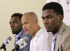 New Charlotte Hornets players P.J. Hairston, left, and Noah Vonleh, right, look on as general manager Rich Cho, center, answers a question during a new conference in Charlotte, N.C., Friday, June 27, 2014. (AP Photo/Chuck Burton)