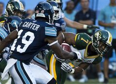 Edmonton Eskimos running back Hugh Charles, right, breaks a tackle from Toronto Argonauts defensive back Jalil Carter, left, during first half CFL football action in Toronto, on Sunday, August 18, 2013. THE CANADIAN PRESS/Nathan Denette