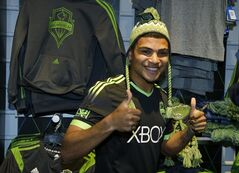 FILE - In this March 3, 2014 file photo, Seattle Sounders' DeAndre Yedlin adds a hat to his modeling of the MLS soccer team's new