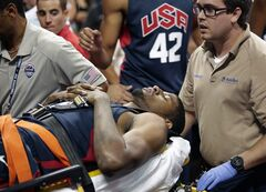 FILE - In this Aug. 1, 2014, file photo, Indiana Pacers' Paul George is taken off the court after he was injured during the USA Basketball Showcase game in Las Vegas. The NBA is expanding the area that must be clear behind the basket and cutting the number of photographers along the baseline in an effort to improve player safety. The new regulations, calling for an extra foot of open space on both sides of the basket stanchion, were sent to teams Tuesday, Aug. 26, 2014, by league president of operations Rod Thorn in a memo that was obtained by The Associated Press. (AP Photo/John Locher, File)