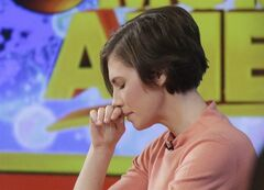 Amanda Knox puts her hand to her face while making a television appearance, Friday, Jan. 31, 2014 in New York. Knox said she will fight the reinstated guilty verdict against her and an ex-boyfriend in the 2007 slaying of a British roommate in Italy and vowed to