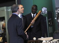 President Barack Obama, accompanied by Baseball Hall of Fame President Jeff Idelson,left, and hall of fame member Andre Dawson, inducted in 2010, holds up Babe Ruth's bat during a tour the Baseball Hall of Fame in Cooperstown, N.Y., Thursday, May 22, 2014. Obama visited the museum to highlight tourism and steps to help spur international visits to the 50 states. Obama said the overall U.S. economy and local businesses will benefit if it isn't a hassle for people from other countries to visit the U.S. and spend money at its hotels, restaurants, tourist destinations and other businesses. (AP Photo/Susan Walsh)