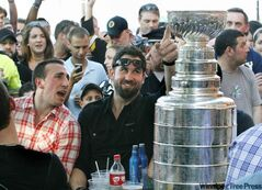 Boston Bruins' Brad Marchand, left, and Shane Hnidy sit at a table with the Stanley Cup while onlookers gather at Tia's Restaurant in Boston Thursday, June 16, 2011.