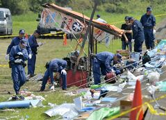 Police investigators gather at the site of a Thursday's blast in Kyoto, western Japan, Friday, Aug. 16, 2013. An explosion at a summer fireworks festival near Kyoto, Japan, has injured 59 people, Japanese media reported. (AP Photo/Kyodo News) JAPAN OUT, MANDATORY CREDIT