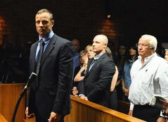 FILE - In this photo taken Tuesday, Feb. 19, 2013 Olympian Oscar Pistorius stands following his bail hearing, as his brother Carl, center, and father Henke look on, in Pretoria, South Africa. The family of Oscar Pistorius, the double-amputee Olympian charged with murdering his girlfriend, is feuding publicly about whether guns are a necessary protection against crime in South Africa. British newspapers quoted Pistorius' father, Henke Pistorius, as saying the family owned handguns for self-defense and suggesting that South Africa's government shares blame for