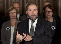 Standing infront of MP's wearing a black hole patch, NDP leader Tom Mulcair speaks with the media in the foyer of the House of Commons Wednesday February 27, 2013 in Ottawa. The black hole patch symbolizes the period of time seasonal recipients are ineligible for benefits. THE CANADIAN PRESS/Adrian Wyld
