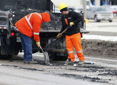 A pothole-fixing crew fills in some of the many holes on the notoriously pockmarked St. James Street Tuesday.