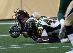 Winnipeg returner Paris Cotton grimaces in pain after Deon Lacey's helmet-popping hit during a first-quarter kickoff return Thursday night.